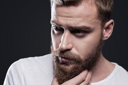 barbero: Perdido en pensamientos. Retrato del hombre barbudo joven pensativa mirando a otro lado y de la mano en la barbilla mientras est� de pie contra el fondo gris