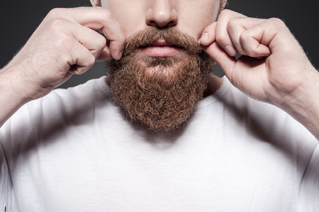 barber: Making his own style. Close-up of young bearded man adjusting his mustaches while standing against grey background