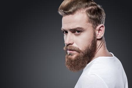 barbero: Confiados en su mirada. Hombre barbudo joven pensativa mirando por encima del hombro mientras est� de pie contra el fondo gris
