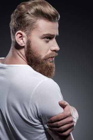 ハンサムなひげを生やした。灰色の背景に敵対しながら肩越しに見ている思いやりのある若いひげを生やした男の後姿