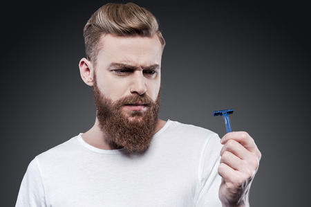 This will not work. Frustrated young bearded man holding razor and looking at it with uncertainty while standing against grey background Foto de archivo