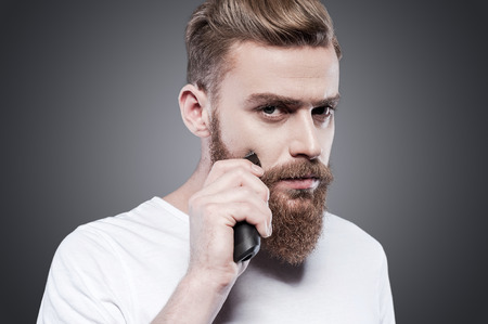 electric razor: Making his beard perfect. Confident young bearded man shaving with electric razor and looking at camera while standing against grey background Stock Photo