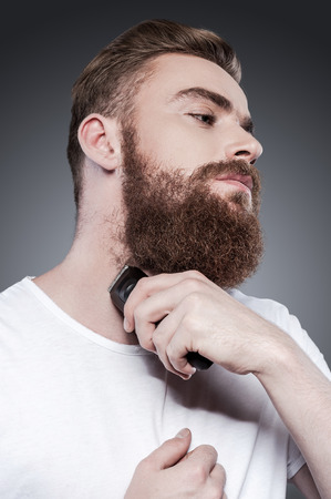 electric razor: Making beard perfect. Confident young bearded man shaving with electric razor while standing against grey background