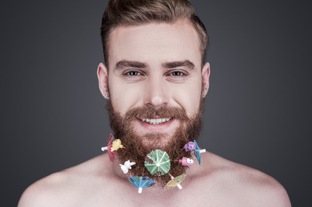 only man: Funky beard. Portrait of handsome young shirtless man with toys and cocktail parasols in his beard looking at camera and smiling while standing against grey background Stock Photo