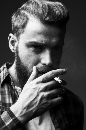 one man only: Bearded man smoking. Black and white portrait of handsome young bearded man smoking a cigarette and looking at camera while standing against grey background