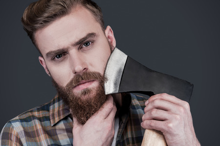 Shaving with axe. Confident young bearded man carrying a big axe on shoulder and looking at camera while standing against grey background photo