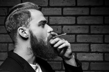 black sex: Man smoking. Black and white portrait of handsome young bearded man smoking a cigarette while standing against brick wall