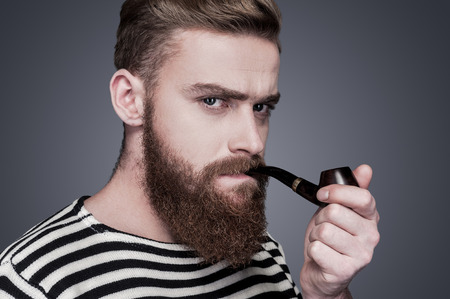 Sailor with pipe. Confident young bearded man in striped clothing smoking a pipe and looking at camera while standing against grey background Stock Photo