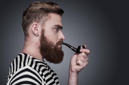 hombre barba: Confiado marinero. Vista lateral del hombre barbudo joven confía en la ropa de rayas fumando una pipa y mirando a otro lado mientras está de pie contra el fondo gris