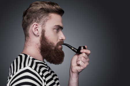 Confident sailor. Side view of confident young bearded man in striped clothing smoking a pipe and looking away while standing against grey background Stock Photo