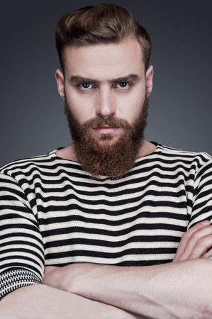 Confidence and masculinity. Confident young bearded man in striped clothing keeping arms crossed and looking at camera while standing against grey background