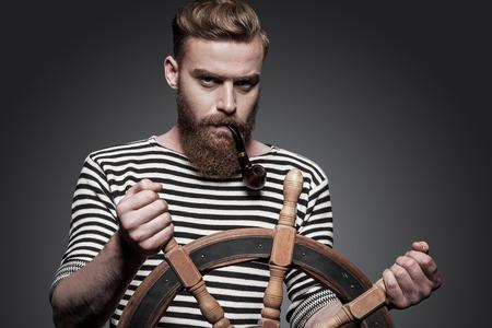 右の方法を見つけます。自信を持って若いひげを生やしたセーラー グレー背景に立っている間ハンドル
