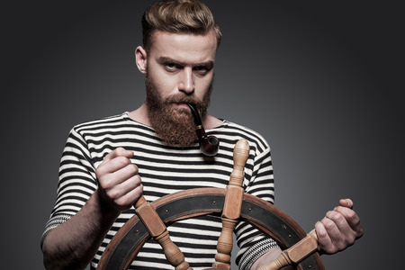 Finding the right way. Confident young bearded sailor steering a wheel while standing against grey background