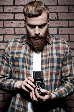 photography themes: Old-fashioned photographer. Handsome young bearded man holding hands in pockets and looking at camera while standing against grey background