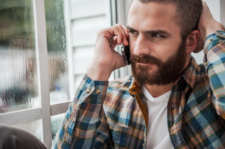 Bad news. Depressed young bearded man expressing negativity while talking on the mobile phone and looking through window photo