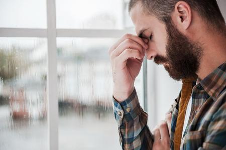 dolor de cabeza: Sentimientos de desesperanza. Hombre barbudo joven deprimido ojos manteniendo cerrados y tocar su cara mientras est� de pie cerca de la ventana