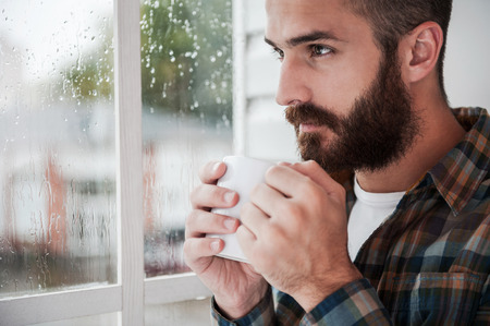 Inspired by rain. Thoughtful young bearded man holding cup with hot drink and looking through window