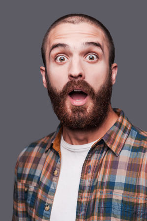 surprise face: It is just unbelievable! Shocked young bearded man keeping arms crossed and expressing ironic smile while standing against grey background Stock Photo