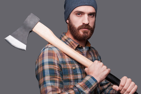 Ready to work. Side view of confident young bearded man holding a big axe and looking at camera while standing against grey background photo