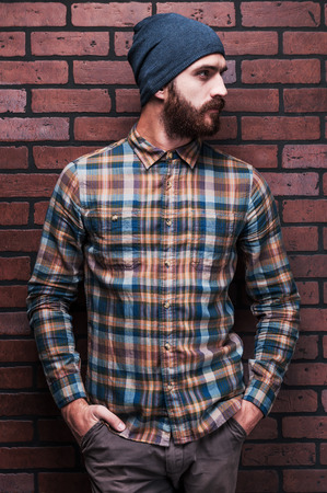 hombre con barba: Hombre hermoso en estilo. Hombre barbudo joven hermoso que sostiene las manos en los bolsillos y mirando a otro lado mientras está de pie contra la pared de ladrillo