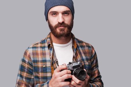 Jistý fotograf. Pohledný mladý vousatý muž drží staromódní kameru a díval se na kameru, když stál na šedém pozadí