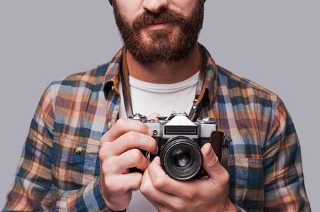 hombre con barba: Sonríe a la cámara! Primer plano de hombre barbudo joven que sostiene la cámara pasada de moda de pie sobre fondo gris