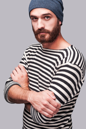 only man: Who is the man? Confident young bearded man in striped clothing keeping arms crossed and looking at camera while standing against grey background