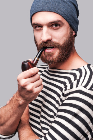 Sailor style. Confident young bearded man in striped clothing smoking a pipe and looking at camera while standing against grey background photo