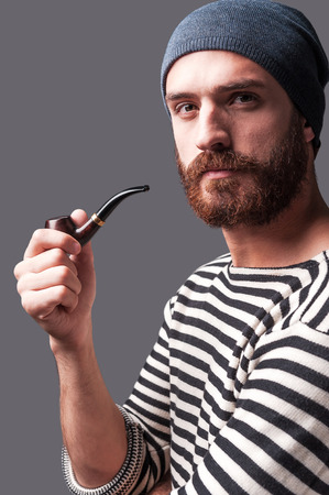 Me and my pipe. Side view of confident young bearded man in striped clothing holding a smoking pipe and looking at camera while standing against grey background photo