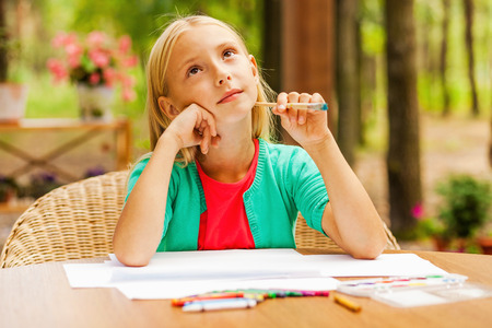 creative thinking: Looking for inspiration. Thoughtful little girl holding hand on chin and looking away while sitting at the table with colorful pencils and paper laying on it