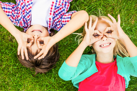 making fun: Summer fun. Top view of two cute little children making faces and smiling while lying on the green grass together Stock Photo