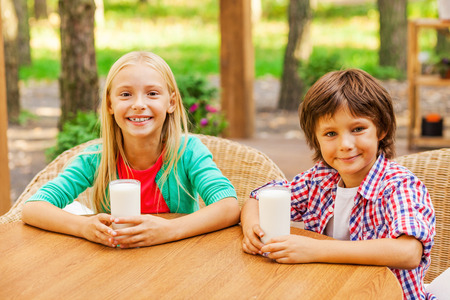 Reloading energy with fresh milk. Two cute little children drinking milk and smiling while sitting outdoors together photo