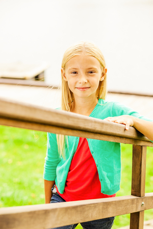 only girls: Cute little girl. Top view of cute little girl moving up by outdoor wooden stairs and smiling Stock Photo