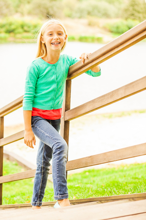 cute little girl smiling: Cute little girl. Top view of cute little girl moving up by outdoor wooden stairs and smiling Stock Photo