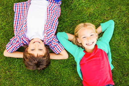 two boys: Enjoying summer time. Top view of two cute little children holding hands behind head and smiling while lying on the green grass together Stock Photo