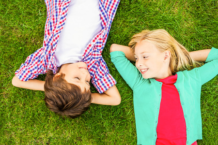 lying on back: Enjoying summer time. Top view of two cute little children holding hands behind head and looking at each other with smile while lying on the green grass together