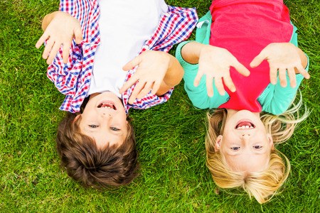 We love summer! Top view of two cute little children raising their hands up and smiling while lying on the green grass together Imagens