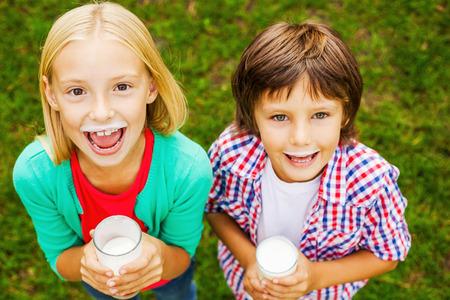 leche: Nos encanta la leche. Vista superior de dos peque�os ni�os lindos con bigotes de leche sostienen los cristales con leche y sonriendo mientras est� de pie sobre la hierba verde juntos