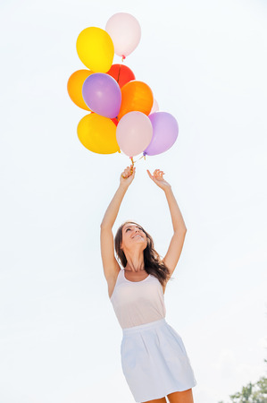 baclground: Balloon fun. Low angle view of young beautiful women holding colorful balloons with sky as baclground Stock Photo