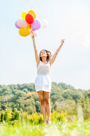 air jump: Flying away. Happy young woman holding colorful balloons and flying over a green meadow