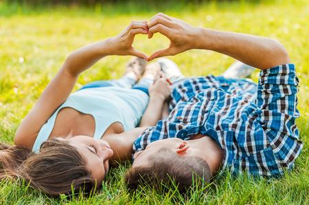 silhouette coeur: Symbole de l'amour. Couple faisant forme de coeur avec les mains, allong� sur l'herbe