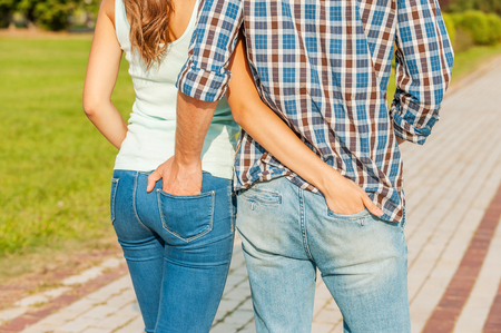 Belong to each other. Young loving couple holding their hands in the pockets of each others jeans while walking. photo