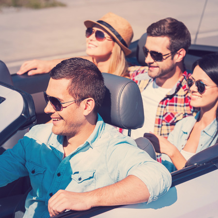 Traveling with fun. Top view of young happy people enjoying road trip in their white convertible photo