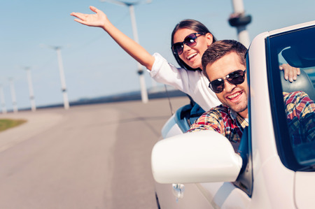 road of love: Fun ride. Happy young couple enjoying road trip in their white convertible Stock Photo