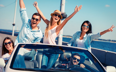 five people: Friends in convertible. Group of young happy people enjoying road trip in their white convertible and raising their arms