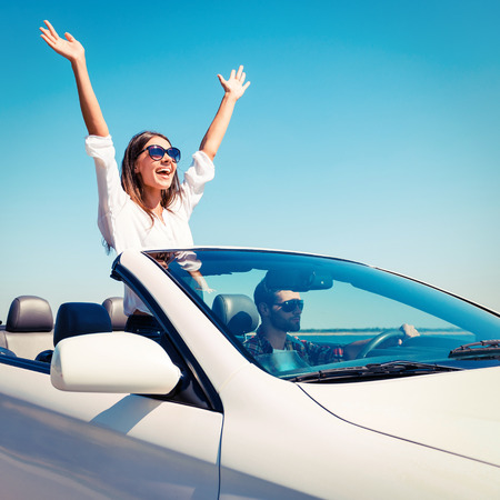 Couple in convertible. Happy young couple enjoying road trip in their convertible while woman raising arms and smiling photo