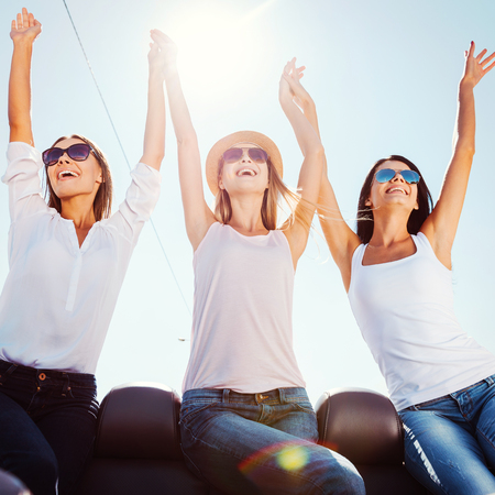 What a beautiful day! Low angle view of three beautiful young women enjoying road trip in convertible and raising their arms photo