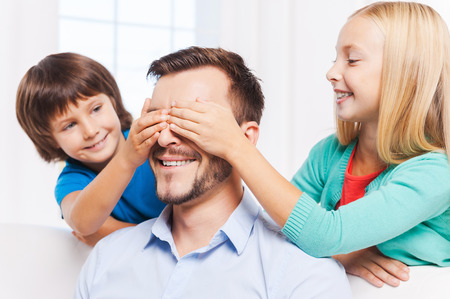 eye's closed: Guess who? Two playful kids covering eyes of their cheerful father and smiling