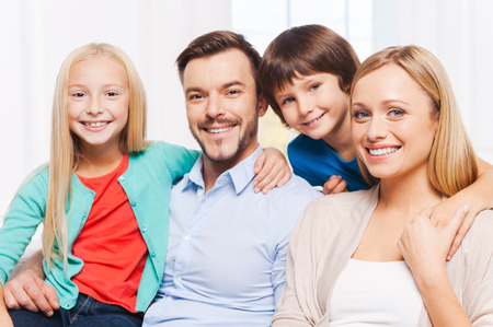 Happy to be a family. Happy family of four bonding to each other and smiling while sitting indoors