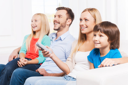 tv home: Watching their favorite show. Side View of happy family of four bonding to each other and smiling while watching TV at home together